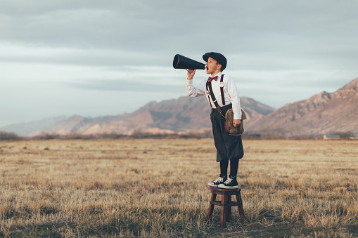 Picture of an old style paper boy standing on a stool in the the middle of a meadow. He is holding a megaphone to his mouth. There are mountains in the background.